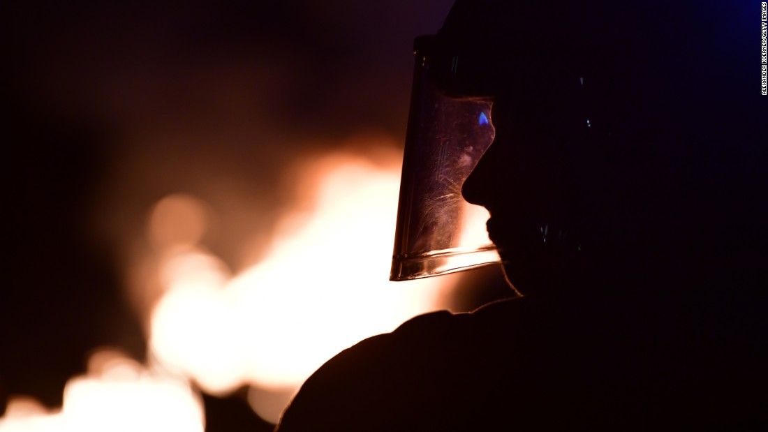 An officer looks on as barricades burn in front of the Rote Flora center.