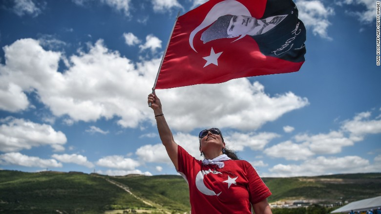 A protester waves a Turkish flag with the nation's founder, Mustafa Kemal Ataturk, superimposed on it.
