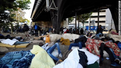 "Migrants and refugees rest on the ground and on mattresses by a railway bridge during the evacuation of a makeshift camp at Porte de la Chapelle, northern Paris, on July 7, 2017, one of several camps sprouting up around the French capital. French authorities proceeded to the evacuation of more than 2,000 migrants settled in a makeshift camp in the north of Paris, a few days before the presentation of a ""migrant plan""  by the government. / AFP PHOTO / Eric FEFERBERG        (Photo credit should read ERIC FEFERBERG/AFP/Getty Images)"