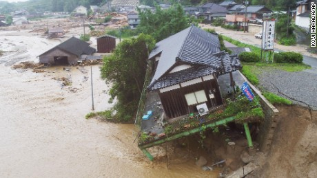 A house tilts off the side of the road in flood and landslide-stricken Asakura in southwest Japan.