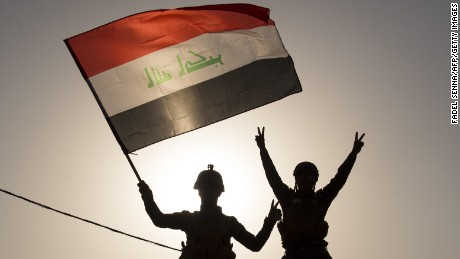 "TOPSHOT - Iraq's federal police members wave Iraq's national flag as they celebrate in the Old City of Mosul on July 9, 2017 after the government's announcement of the ""liberation"" of the embattled city.  Iraq declared victory against the Islamic State group in Mosul on July 9 after a gruelling months-long campaign, dealing the biggest defeat yet to the jihadist group. / AFP PHOTO / FADEL SENNA        (Photo credit should read FADEL SENNA/AFP/Getty Images)"
