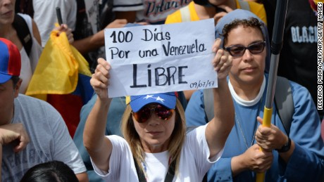 "An opposition activist holds a sign reading ""100 Days For a Free Venezuela"" as she takes part in a demonstration marking 100 days of protests against Venezuelan President Nicolas Maduro in Caracas, on July 9, 2017. Venezuela hit its 100th day of anti-government protests on Sunday, one day after its most prominent political prisoner, Leopoldo Lopez, vowed to continue his fight for freedom after being released from jail and placed under house arrest. At least 91 people have died since non-stop street protests began on April 1. / AFP PHOTO / Federico PARRA        (Photo credit should read FEDERICO PARRA/AFP/Getty Images)"