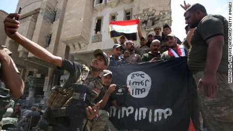 Members of the Iraqi interior ministry forces pose for a picture with an upside down Islamic State (IS) group flag in the Old City of Mosul on July 8, 2017, as their part of the battle has been declared accomplished, while other forces continue to fight the jihadists in the city. / AFP PHOTO / AHMAD AL-RUBAYE        (Photo credit should read AHMAD AL-RUBAYE/AFP/Getty Images)