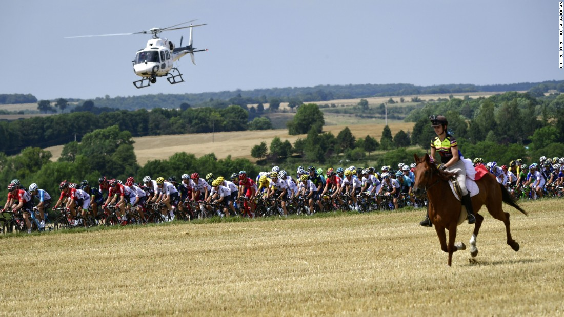A horse rider is pictured in front of the pack as a media helicopter flies overhead during the seventh stage between Troyes and Nuits-Saint-Georges.