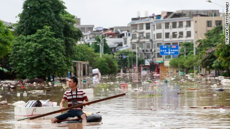 A man using an improvised flotation device in floodwaters in Liuzhou, Guangxi in July 2017.
