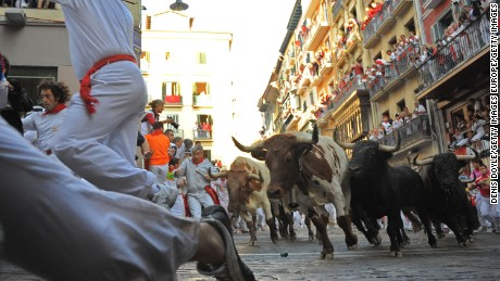 PAMPLONA, SPAIN - JULY 07:  Runners lead  fighting bulls around  a corner at Estafeta street during the 1st day of the San Fermin running of the bulls fiesta  on July 07, 2009 in Pamplona, Spain. People run through the streets of Pamplona with fighting bulls for eight mornings during the San Fermin fiesta which was made famous by Earnest Hemmingway's novel 'The Sun Also Rises'. The bullrun tradition in Pamplona dates back to 1591.  (Photo by Denis Doyle/Getty Images)