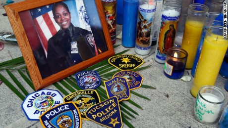 Police department badges adorn a sidewalk memorial  outside the 46th Precinct in the Bronx.