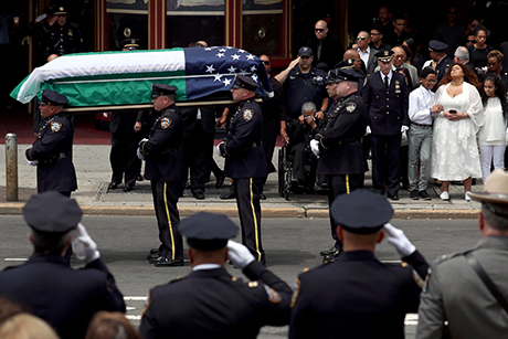 The casket  of  slain New York Police Department Officer Miosotis Familia is carried from the World Changers Church in the Bronx as her children and mother stand nearby.