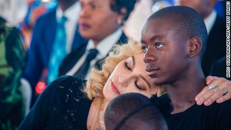 US pop star Madonna (L) rests her head on the shoulder of her adopted son David Banda during the opening ceremony of the Mercy James Children's Hospital at Queen Elizabeth Central Hospital in Blantyre, Malawi, on July 11, 2017. Madonna on July 11 took her four adopted Malawian children back to their home country for the opening of a paediatric hospital wing that her charity has built. / AFP PHOTO / AMOS GUMULIRA        (Photo credit should read AMOS GUMULIRA/AFP/Getty Images)