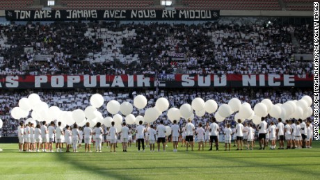 People hold white ballons in the middle of the pitch in tribute to the victims of the Bastille day attack in Nice before the French L1 football match between OGC Nice and Rennes on August 14, 2016, at the Allianz Riviera stadium in Nice, southern France. / AFP / JEAN CHRISTOPHE MAGNENET        (Photo credit should read JEAN CHRISTOPHE MAGNENET/AFP/Getty Images)