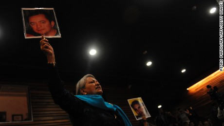 Yolanda Moran holds a picture of her missing son Dan Jeremeel Fernandez, who disappeared on December 19, 2008 in Torreon, Coahuila, as she attends the presentation of the independent inquiry into the massacre of 72 migrants in San Fernando, Tamaulipas in August 2010 and the disappearance of residents of Allende, Coahuila, in 2011, at the Museum of Memory and Tolerance in Mexico City on October 9, 2016. / AFP / Pedro PARDO        (Photo credit should read PEDRO PARDO/AFP/Getty Images)