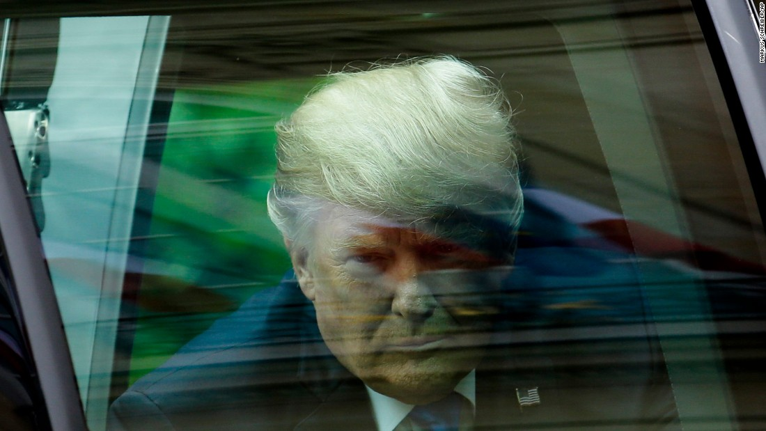 Trump exits his car as he arrives for the meeting in Paris.