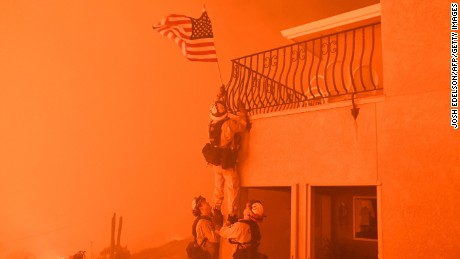 "TOPSHOT - Firefighters remove a US flag as flames from the ""Wall Fire"" close in on a luxury home in Oroville, California on July 8, 2017.