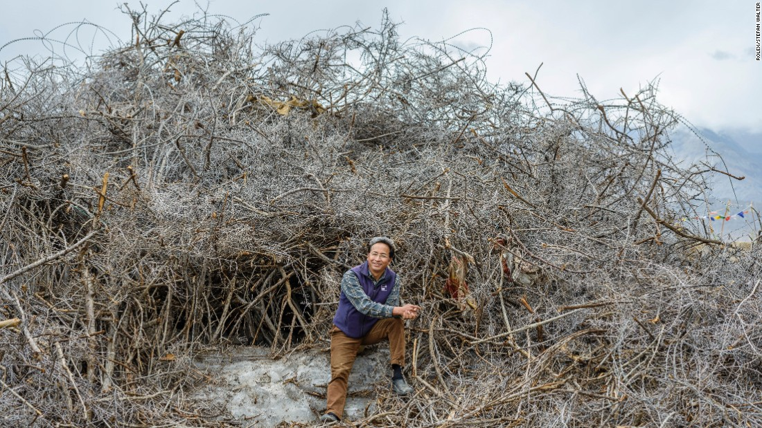 Mechanical engineer Sonam Wangchuk, the inventor of the ice stupa, pictured here with the natural materials, like bushes, that he uses as catalysts to start the ice formation.