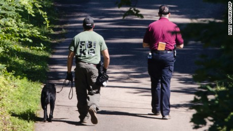 Investigators and a dog walk up a driveway amid the search for four missing young Pennsylvania men.