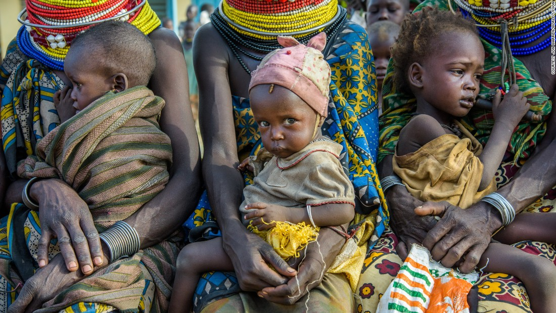 Families wait for malnourished children to be weighed and measured at a health clinic in Kenya.