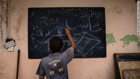 A refugee kid draws in a blackboard inside the school Hag Ali high school for girls. The educational center has been taken over as a collective shelter. The escalation of violence has led to civilian casualties, considerable displacement, destruction of public infrastructure and the disruption of education August, Iraq 2016. Diego Ibarra Sánchez / MeMo