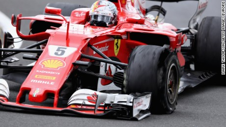 Sebastian Vettel drives his Ferrari with a puncture clearly noticeable on his shredded front left tire.