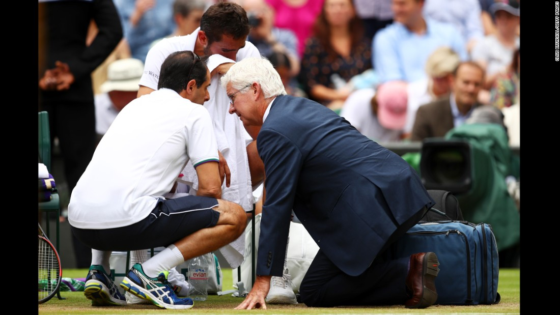An emotional Cilic receives assistance during his loss to Federer.