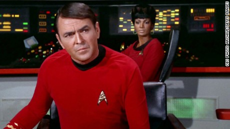 "James Doohan as Montgomery ""Scotty"" Scott on the bridge with Nichelle Nichols as Uhura in the STAR TREK episode, ""A Piece of the Action."""