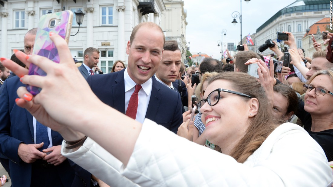 William poses for a selfie with a woman on July 17, as a crowd gathers outside the Presidential Palace in Warsaw, Poland, to greet the royals.