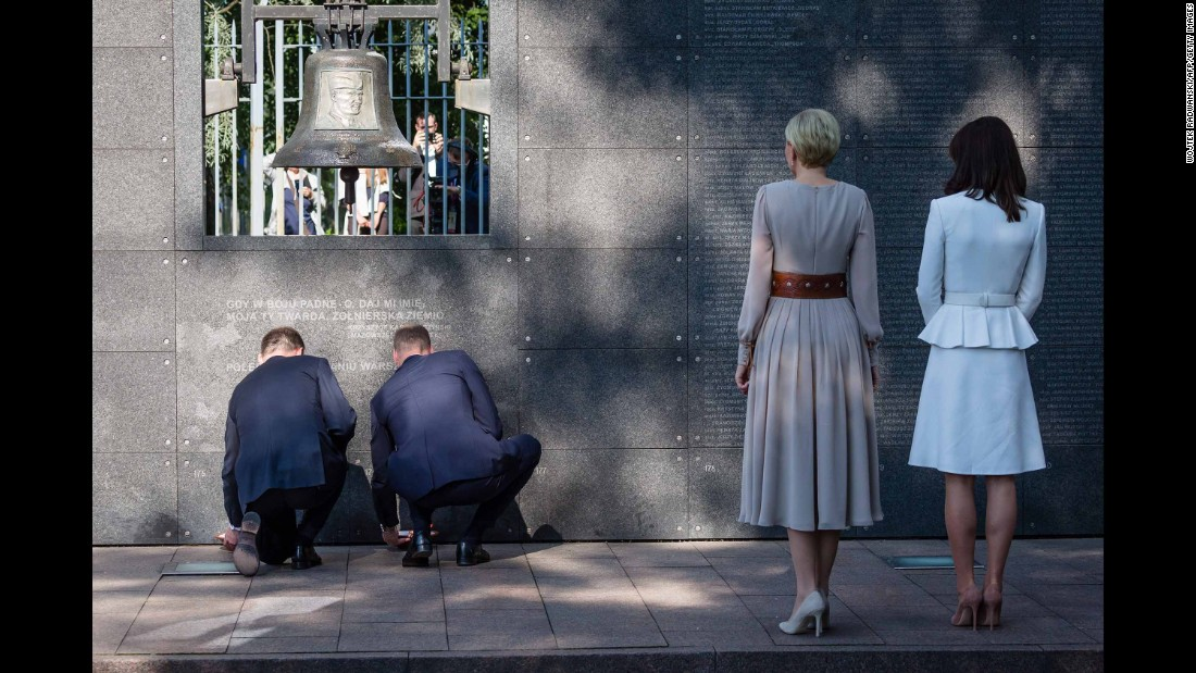 Duda, left, and William, kneel as they light candles during a visit to the Warsaw Uprising Museum while Poland's first lady, second from right, and Kate look on.