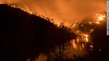 The Detwiller Fire burns around Lake McClure near Bear Valley, California, on Monday, July 17.