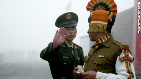 In this photograph taken on July 10, 2008, A Chinese soldier gestures as he stands near an Indian soldier on the Chinese side of the ancient Nathu La border crossing between India and China. When the two Asian giants opened the 4,500-metre-high (15,000 feet) pass in 2006 to improve ties dogged by a bitter war in 1962 that saw the route closed for 44 years, many on both sides hoped it would boost trade. Two years on, optimism has given way to despair as the flow of traders has shrunk to a trickle because of red tape, poor facilities and sub-standard roads in India's remote northeastern mountainous state of Sikkim. AFP PHOTO/Diptendu DUTTA (Photo credit should read DIPTENDU DUTTA/AFP/Getty Images)