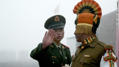 A Chinese soldier gestures as he stands near an Indian soldier on the Chinese side of the ancient Nathu La border crossing between India and China.