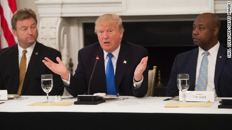 US President Donald Trump speaks alongside US Senator Dean Heller (L), Republican of Nevada, and US Senator Tim Scott (R), Republican of South Carolina, during a meeting with Republican Senators to discuss the health care bill in the State Dining Room of the White House in Washington, DC, July 19, 2017. / AFP PHOTO / SAUL LOEB        (Photo credit should read SAUL LOEB/AFP/Getty Images)