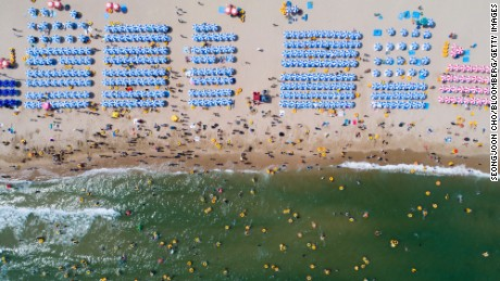 RESTRICTED Bathers are seen on the beach and in the sea in this aerial photograph taken above Haeundae beach in Busan, South Korea, on Sunday, July 16, 2017. South Korea's minimum wage is set to increase next year by 16 percent to 7,530 won ($6.60) per hour, the biggest jump since 2001, giving President Moon Jae-in an early victory in his push to boost incomes. Photographer: SeongJoon Cho/Bloomberg via Getty Images