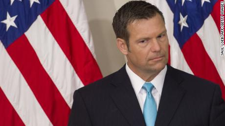 Kansas Secretary of State Kris Kobach listens as US President Donald Trump speaks during the first meeting of the Presidential Advisory Commission on Election Integrity in the Eisenhower Executive Office Building next to the White House in Washington, DC, July 19, 2017. / AFP PHOTO / SAUL LOEB        (Photo credit should read SAUL LOEB/AFP/Getty Images)