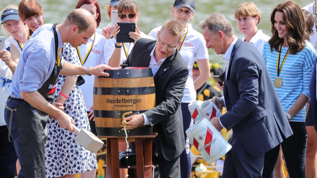 Prince William hammers a tap into a beer barrel as Kate, far right, watches on July 20 in Heidelberg, Germany.