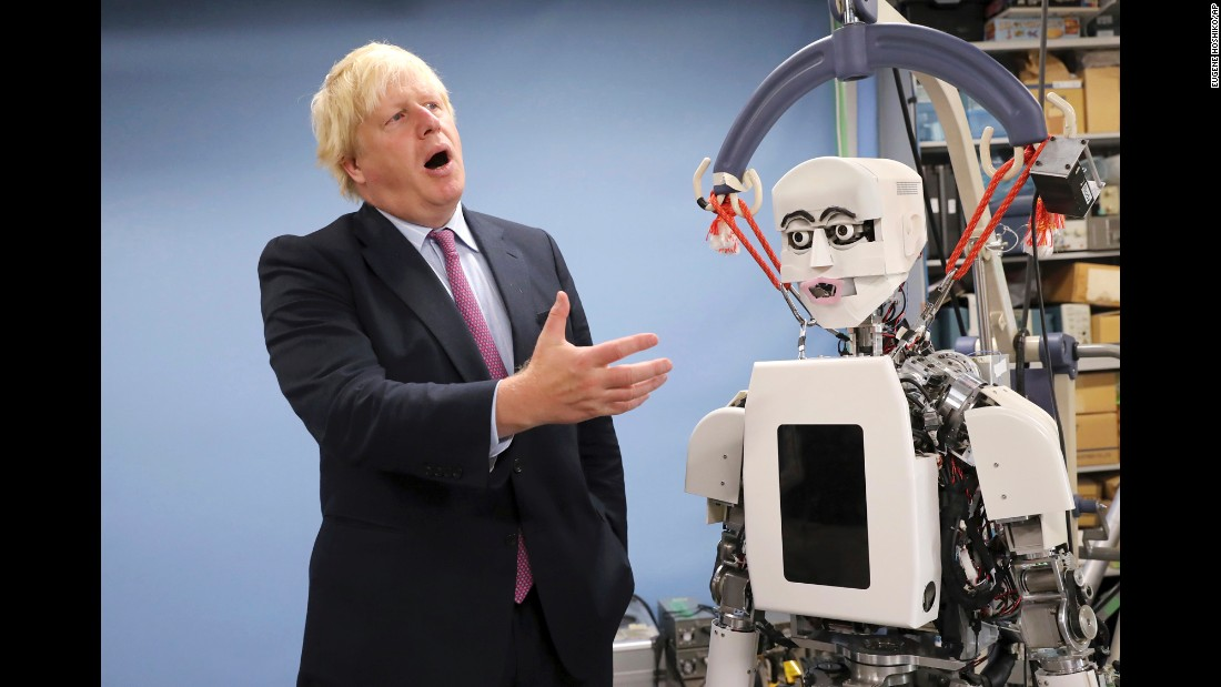 Britain's Foreign Secretary Boris Johnson gestures as he looks at a humanoid robot at the Research Institute for Science and Engineering at Waseda University in Tokyo on Thursday, July 20. The robotics center at Waseda University collaborates with the University of Birmingham, according to Britain's Foreign and Commonwealth Office.