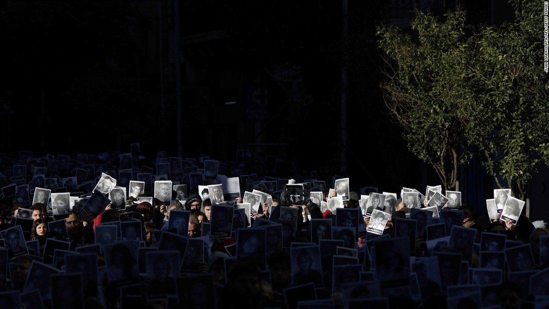 People hold portraits showing victims during the 23rd anniversary of the terror attack against the Argentine Israelite Mutual Association Jewish community center in Buenos Aires on Tuesday, July 18. The bombing left 85 people dead and 300 injured.