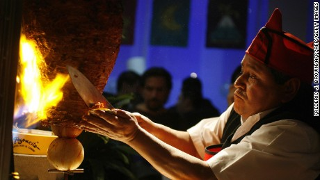 Beijing, CHINA: Mexican chef Alberto Juarez Don Beto slices grilled meat onto a hand-held tortilla for a taco al pastor, 30 January 2007 in Beiijng, during an opening-event for Mexican restaurant El Fogoncito.  The popular Mexican taco chain, first established in 1968 in Mexico City, the same year Mexico hosted the Olympics, has opened its first restaurant in China and announced plans to follow with 25 more eateries over the next four years in Beijing and Shanghai.  AFP PHOTO/Frederic J. BROWN (Photo credit should read FREDERIC J. BROWN/AFP/Getty Images)