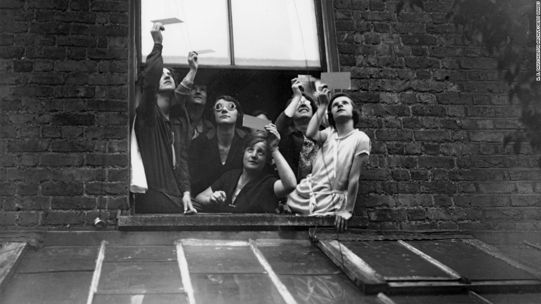 There's no sense of wonder or excitement here. Even as recently as the 1920s, eclipses were still regarded with fear. This group gathered in a window to view the total solar eclipse over London through smoked glass -- touted as a safe method at the time -- in June 1927.