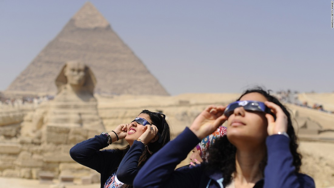 People use protective glasses to catch a glimpse of a solar eclipse in front of Pyramids of Giza and the Sphinx on March 20, 2015 in Giza, Egypt.