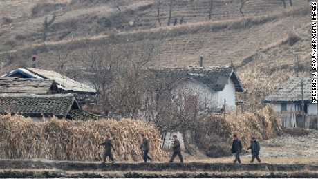 "North Korean men walk amid a dry and barren landscape on the banks of the Yalu River some 70 kms north of Dandong in northeast China's Liaoning province which lies across the river from the North Korean border town of Siniuju on November 24, 2010. Chinese state media coverage of the Korean peninsula shelling incident has avoided criticising Beijing's close ally Pyongyang and even said the episode showed North Korea's ""toughness"" after the reclusive communist state fired a deadly barrage of artillery shells onto a South Korean island on November 23 in one of the most serious border incidents since the 1950-1953 war, sparking global condemnation of Pyongyang.  AFP PHOTO/Frederic J. BROWN (Photo credit should read FREDERIC J. BROWN/AFP/Getty Images)"