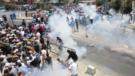 Palestinians run away from tear gas thrown by Israeli police officers outside Jerusalem's Old City, Friday, July 21, 2017. Israel police severely restricted Muslim access to a contested shrine in Jerusalem's Old City on Friday to prevent protests over the installation of metal detectors at the holy site. (AP Photo/Mahmoud Illean)