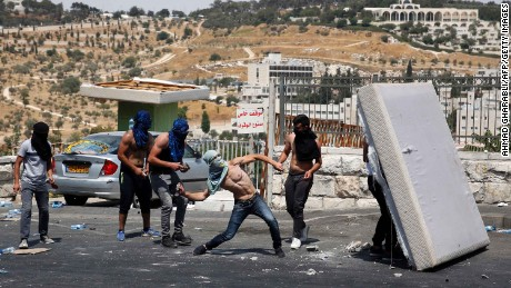 A Palestinian youth hurls rocks towards Israeli security forces outside Jerusalem's Old City on Friday, 21 July.