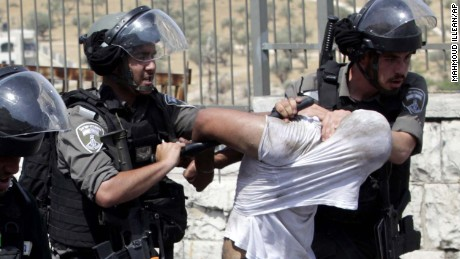 Israeli border police officers detain two Palestinians during clashes in Jerusalem on Friday, July 21, 2017. Thousands of Muslims prayed Friday in the streets outside Jerusalem's Old City after Israeli police barred men under 50 from entering the Old City for Friday prayers on July 21, 2017. (AP Photo/Mahmoud Illean)