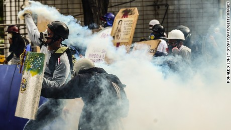 Opposition demonstrators clash with riot police during an anti-government protest in Caracas, on July 20, 2017.  A 24-hour nationwide strike got underway in Venezuela Thursday, in a bid by the opposition to increase pressure on beleaguered leftist President Nicolas Maduro following four months of deadly street demonstrations. / AFP PHOTO / RONALDO SCHEMIDT        (Photo credit should read RONALDO SCHEMIDT/AFP/Getty Images)