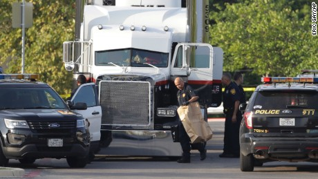 San Antonio police officers investigate the scene where eight people were found dead in a tractor-trailer loaded with at least 30 others outside a Walmart store in stifling summer heat in what police are calling a horrific human trafficking case, Sunday, July 23, 2017, in San Antonio.