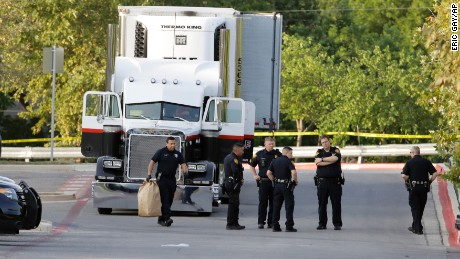 San Antonio officers investigate the scene where eight people were found dead in a tractor-trailer outside a Walmart.