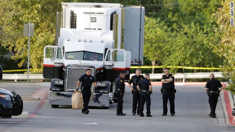 San Antonio police officers investigate the scene Sunday, July 23, 2017, where eight people were found dead in a tractor-trailer loaded with at least 30 others outside a Walmart store in stifling summer heat in what police are calling a horrific human trafficking case,  in San Antonio.