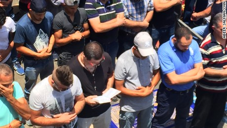 Nidal Aboud a Christian man hold a bible and prays among Muslims to show solidarity in Jerusalem, where there have been clashes between Israeli forces and Palestinians.