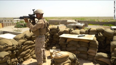 A US Marine in Helmand Province, Afghanistan, looks out through the scope of his assault rifle.