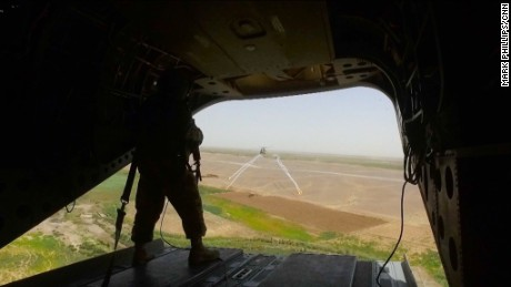A US Marine stands at the back of a Chinook helicopter en route to Shorsharak.