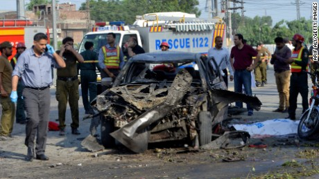 Pakistani security officials inspect the site of the explosion.